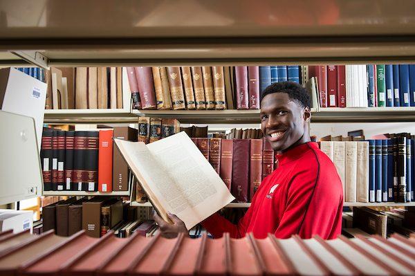Badger men's basketball player Nigel Hayes browses book in Memorial Library